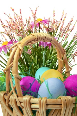 Easter colored eggs in the basket on the white background  photo