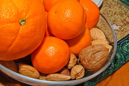 Tangerines, oranges and nuts in bowl on the table.