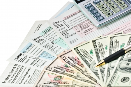 tax: Tax forms 1040 with pen, calculator and money.