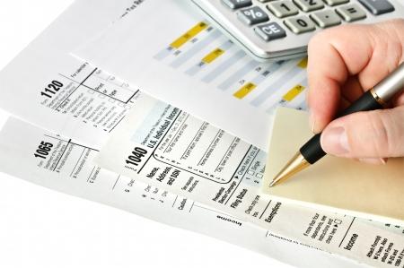 contabilidad: Los formularios de impuestos con la pluma, calculadora y etiqueta. Aislado.