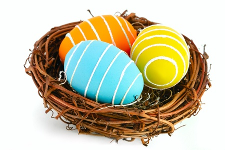 Colored Easter eggs in a nest on a white background