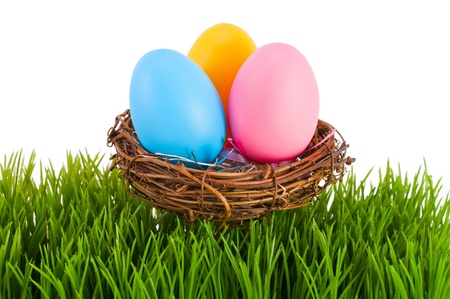Colored Easter eggs in a nest on a white background.