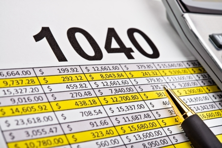 spread sheet: Tax forms 1040, spread sheet with pen and calculator.