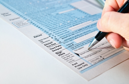 taxation: Tax form 1040 with pen in hand.