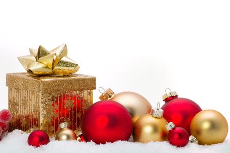 Zblízka dekorativních vánočních ozdob na sněhu.