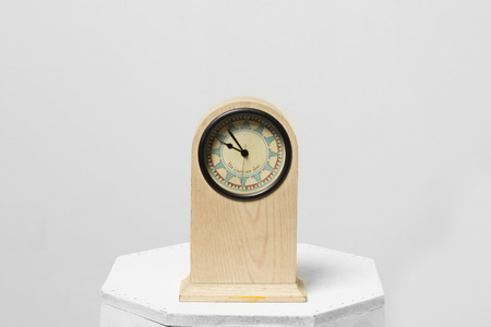 counting five: A vintage clock isolated on gray background.