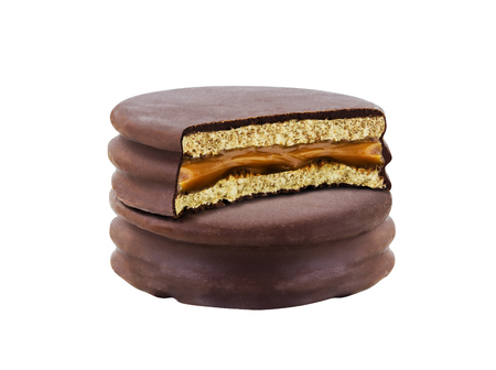 alfajor: advice with bite chocolate alfajor biscuit cookie, caramel filled and white background