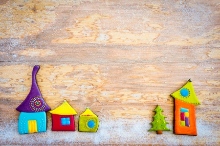 Sweet village  Colorful christmas cookies on wooden background photo