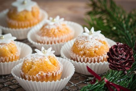 ittle: Little cupcakes decorated with powdered sugar, ittle gumpaste flowers, stars and sugar pearls  Selective focus