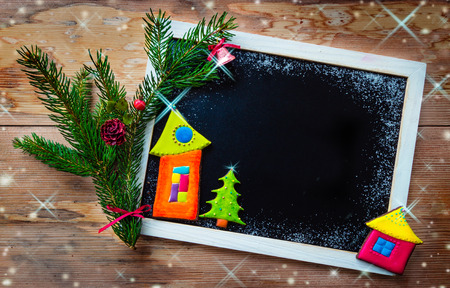 Blackboard decorated with colorful cookies and fir tree branch photo
