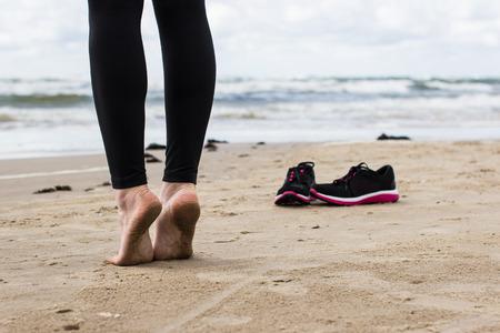 close-up dos pés descalços de Gil na praia. Imagens