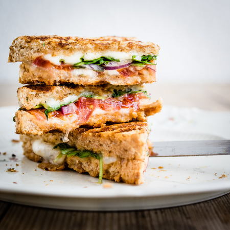 sandwich: Vegetarian panini with tomatoes and mozzarella on rustic wooden table. Selective focus.