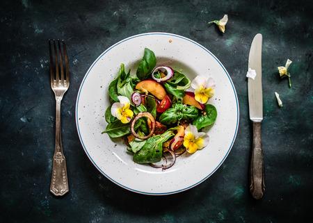 salad in plate: Ensalada de verano Coloful con nectarinas y flores comestibles. Vista superior.