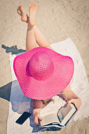 pink hat: Young female hidden under big pink hat relaxing on the beach