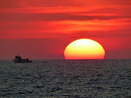 太陽は赤い空で海に沈む 写真素材