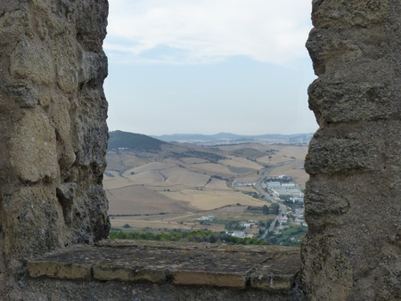 Andalusian landscape seen from a stone window in a castle, Spain
