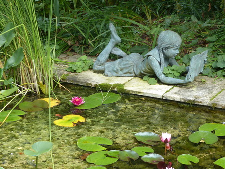 Statue of a little girl with lying braids reading in edge of a pond of water lilies Banque d'images - 102147129