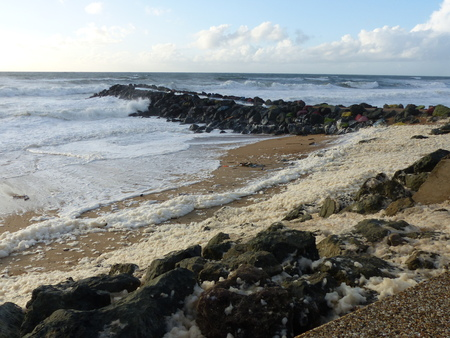 Beach with rocks and white foam of the waves of the rough sea at Biarritz in France.