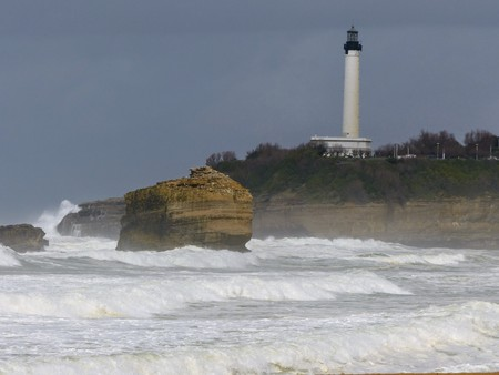 Rock on the sea with a white lighthouse behind the stormy sea at Biarritz in France. Stock Photo