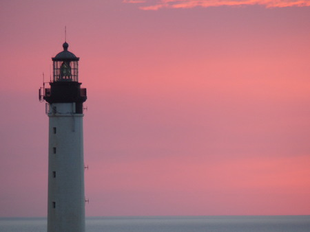 Extremity of a white lighthouse at sunset with a pink sky