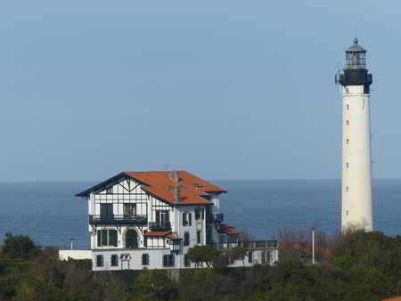 White lighthouse with beside a characteristic house of the French Basque country with the sea at the bottom of Biarritz in France. Stock Photo
