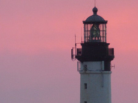 Extremity of a white lighthouse in a pink sky at sunset Stock Photo