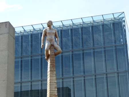 Statue of a naked native man at the end of a column in front of the Egyptian museum of Munich in Germany.