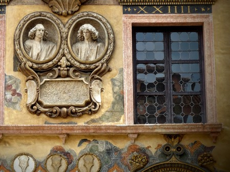 Window decorated with medallions of two busts of statues in Piazza dei Signori in Verona, Italy