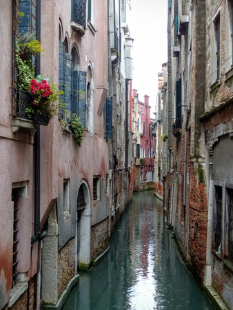 Narrow canal in Venice with ancient buildings facing each other, Italy Archivio Fotografico - 115764356