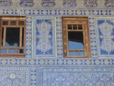 Wooden windows with a majolica wall at Khiva in Uzbekistan.