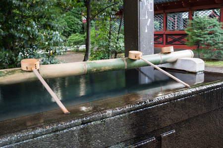 TOKYO - CIRCA JUNE 2014: Cleansing basin in Shinto temple. Shrine attendees must perform purification before entering on circa June 2014