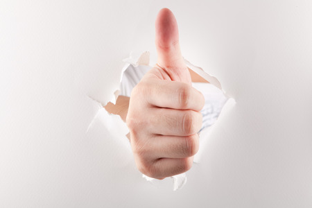 Thumbs up through paper