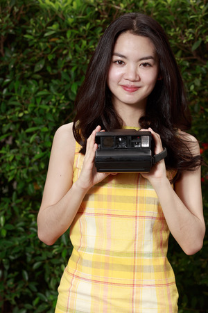 Asian woman happily using a retro camera photo