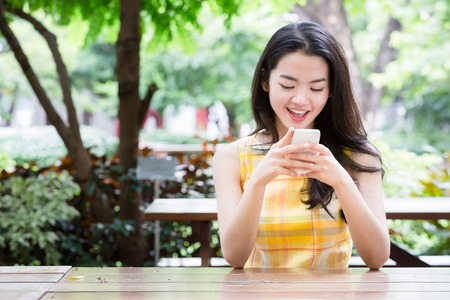 happily: Young asian woman happily using a smart phone Stock Photo