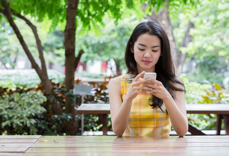 chinese woman: Young asian woman happily using a smart phone Stock Photo