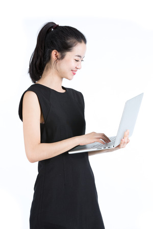 Asian business woman using a laptop, standing photo