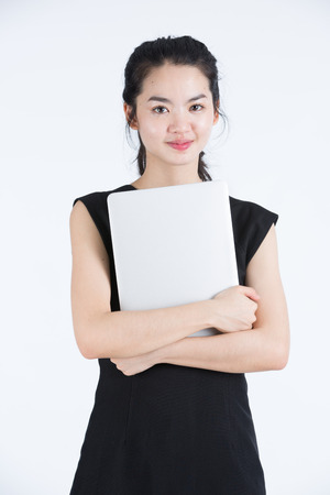 Asian business woman holding a laptop, standing photo