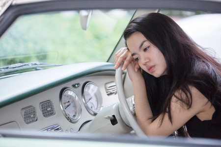 Asian lady smiling in a vintage car photo