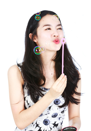 blowing bubbles: Young aisan lady blowering bubbles Stock Photo