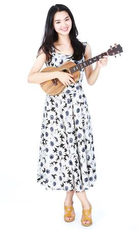 Attractive asian girl playing ukulele
