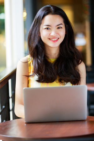 Asian woman happily using a notebook photo