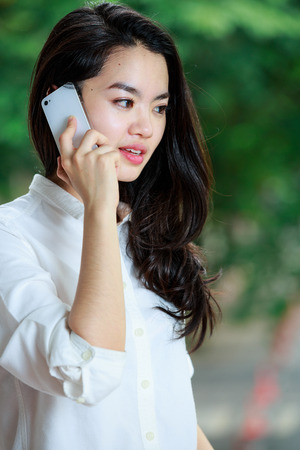 lady on phone: Asian lady in casual clothes using a mobile phone
