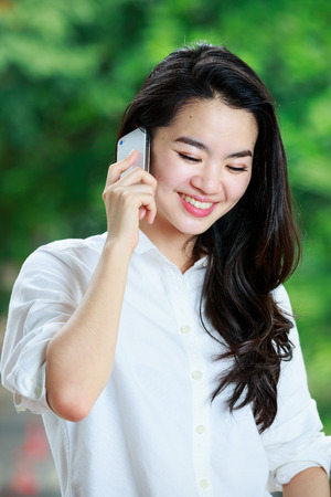 Asian lady in casual clothes using a mobile phone photo