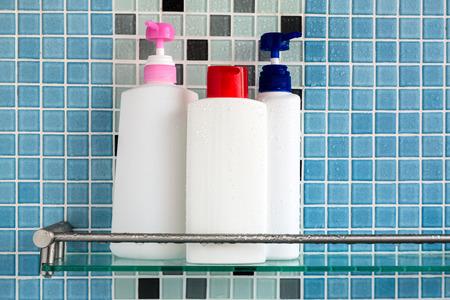 champu: Grupo de botellas de champú en el baño