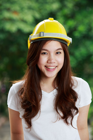 Beautiful young thai engineer with hard hat in jeans photo