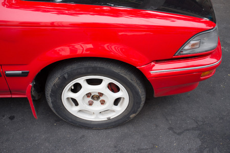 Red old car with tyre and white rim photo