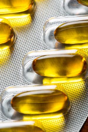Golden oil viltamin pill - close up Stock Photo