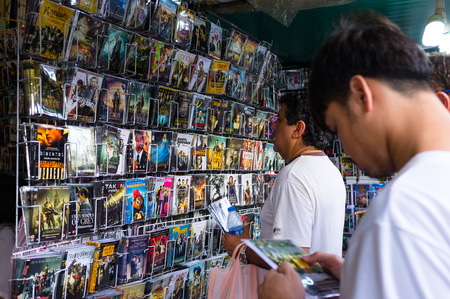 pirated: BANGKOK, THAILAND - CIRCA JULY, 2015: Unidentified tourists buying pirated movie from Chatuchak weekend market.
