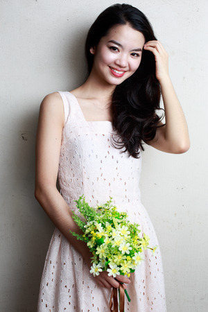 hand holding flower: Asian lady holding a bunch of flower standing against a wall