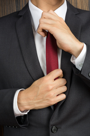 correcting: Asian man in a suit correcting his red necktie